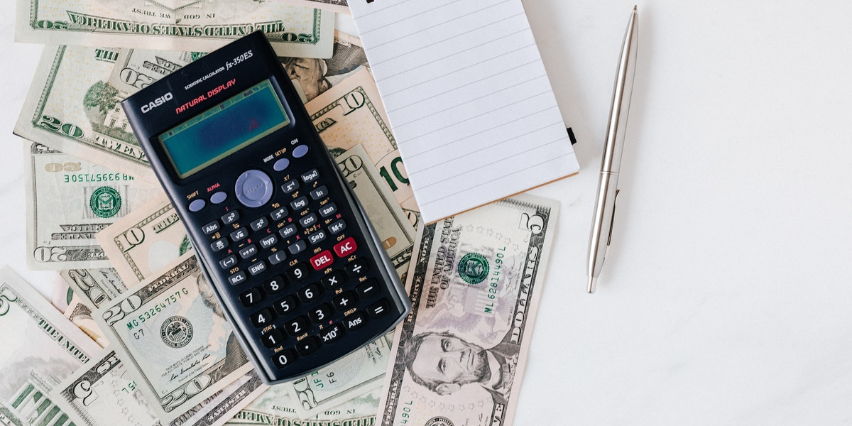 Taking your finances seriously money, calculator, notepad and a pen