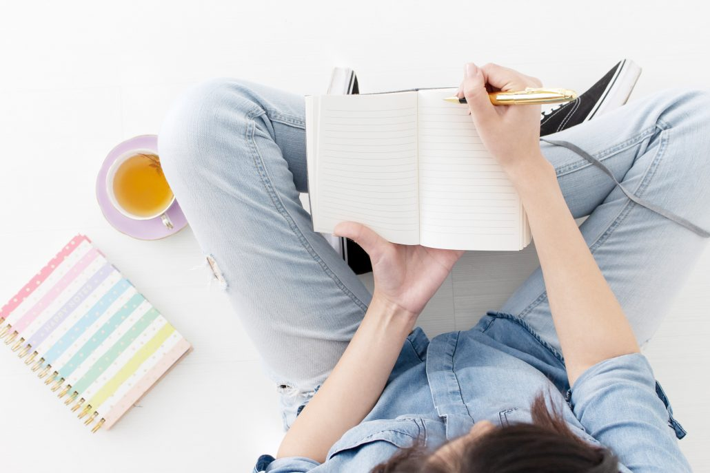 A girl sitting on a floor wearing blue denim writing in a journal.